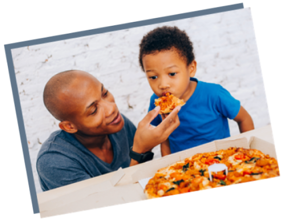 A dad feeds his son pizza baked on a Chicago Metallic pizza pan
