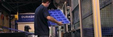A technician at DuraShield examines a pan